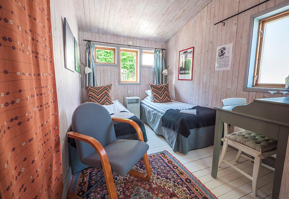 Tvåbäddsrum på hotell med fåtölj i förgrund