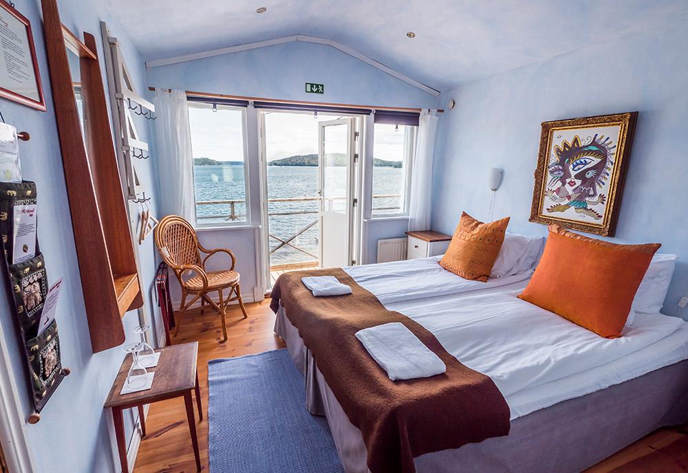 hotellrum med blå väggar och balkong mot havet